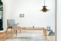 stół kawowy i szary fotel oraz skandynawska lampa