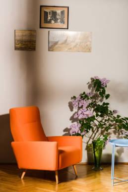 pomarańczowy fotel vintage prl po renowacji z kwiatami bzu
